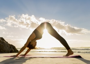 Side view of female athlete doing yoga in downward facing dog position on shore. Sunlight is streaming through young woman exercising at beach during sunset. She is in sportswear.